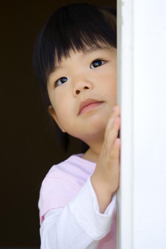 pretty-little-child-stands-behind-a-door-PGA9TAS